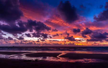 Colorful cloudy twilight sky reflecting to Phuket beach, Thailand at sunset.
