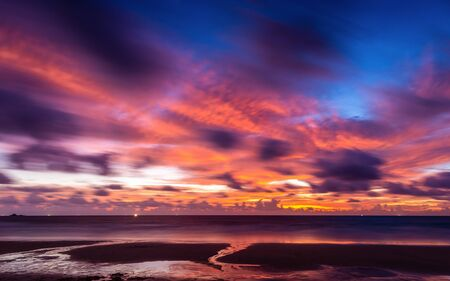 Blurry movement of colorful cloudy twilight sky reflecting to Phuket beach, Thailand at sunset. Banco de Imagens