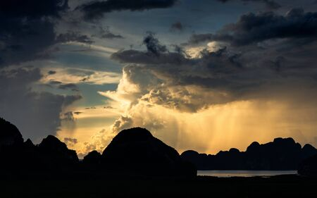 Dark scene of storm which clouds and rain obscured sunlight over silhouetted islands on Sametnangshe gulf, Phangnga, Thailand. Banco de Imagens
