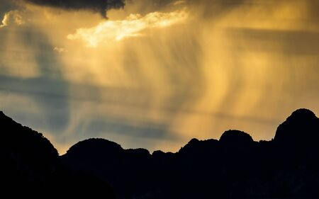 Dark scene of storm which rain obscured sunlight over silhouetted islands on Sametnangshe gulf, Phangnga, Thailand. Banco de Imagens