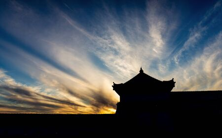 Silhouetted fortress and wall with dramatic cloudy blue sky at sunset. Banco de Imagens