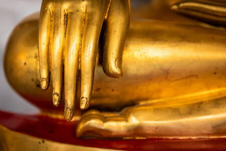 Close focus on hand and fingers of golden buddha statue.
