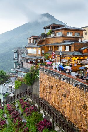 Jiufen, Taiwan - November 9, 2017: Jiufen historical township on hill in north part of Taiwan on cloudy day surrounded by mountains. Tourists walking around with umbrella on rainy day.