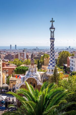 Barcelona, Spain - October 5, 2018: Aerial view on barcelona city with iconic mosaic tower of Park Guell, Gaudis art building and park.