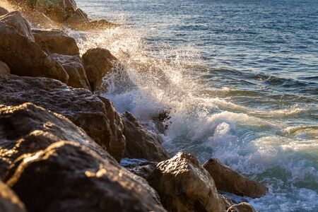 Splashing water from touching of strong wave on rocks with sunlight in behind at sunrise.