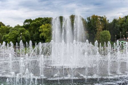 Splashing water of fountain inject from ground showing in public park.