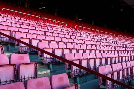 Vacant red chairs of stand inside football stadium. Banco de Imagens