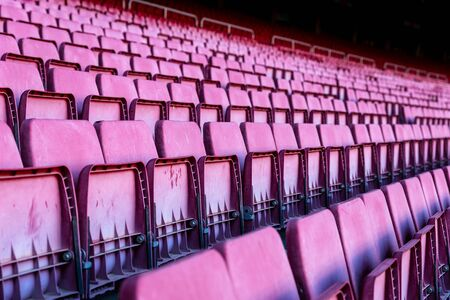 Vacant red chairs of stand inside football stadium. 版權商用圖片