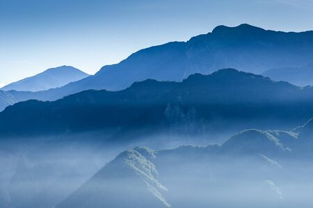 Hazy blue mountain range covered by fog in winter.