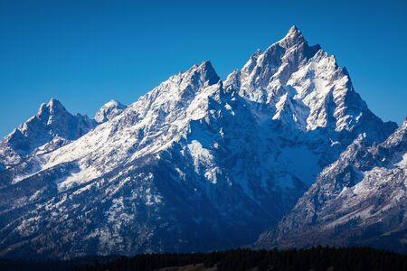 Snow cover mountain peak of Grand Teton outstanding in blue sky of Grand Teton National Park, Wyoming, USA.