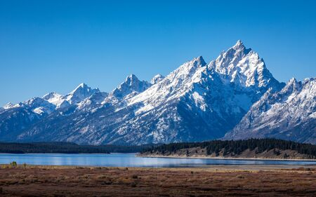 Snow cover mountain peak of Grand Teton outstanding in blue sky beside Jackson Lake and Willow Flats of Grand Teton National Park, Wyoming, USA.