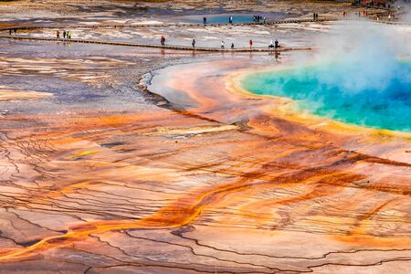 Aerial of Grand Prismatic Spring turning to bright orange and blue when touching sunlight, the popular geyser basin of Yellowstone National Park, USA. Bacteria in water make ground in different color.