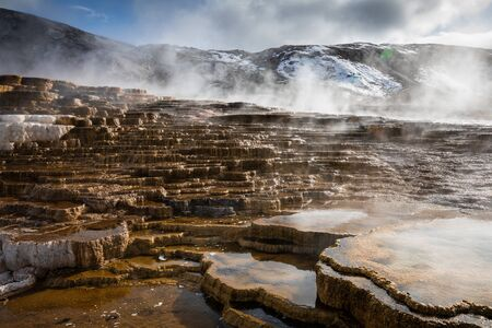 Terraces of Mammoth hot spring made by calcium carbonate covered by smoke from hot water, Yellowstone National Park, Wyoming, USA.