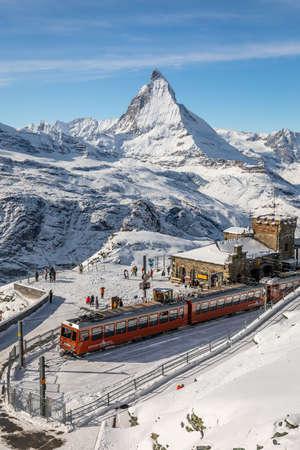 Gornergrat, Zermatt, Switzerland - November 12, 2019: Red cable car train on snowy railway at summit station with tourists and Matterhorn summit in winter.