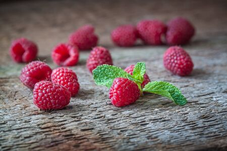 is green: Raspberries with a mint leaf on the wooden background. Closeup.