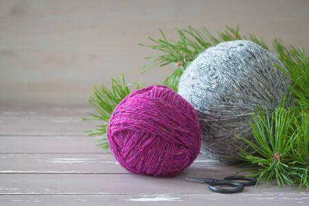 Fuchsia and grey tweed yarn on the wooden background near branches of pine-tree with black vintage scissors Stock Photo