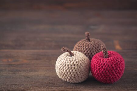 Beige, chocolate and bordo knitted, crocheted apples on wooden background