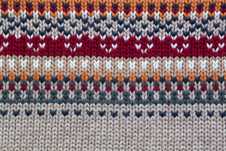 Grey, orange, bordo and beige realistic knitting pattern. Jacquard technic Stockfoto