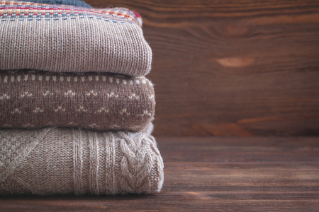 tejido de lana: Pile of beige knitted winter clothes on wooden background, sweaters, knitwear, space for text