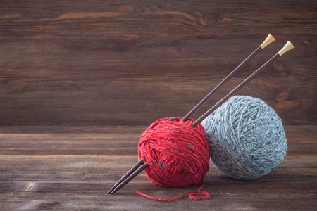 trabajo manual: Red and grey tweed wool yarn with wooden knitting needles Foto de archivo