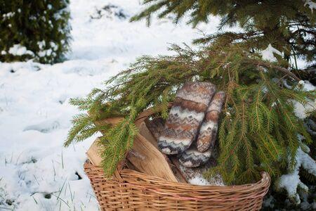 card making: Wool mittens on the basketful of firewood near snowy Christmas-tree. Scandinavian style