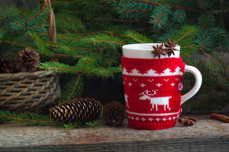 Christmas handmade knitted mug with tea, red ligntning lantern and Santas helper hat on the rustic background Stock Photo