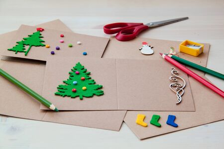 Handtekening Handgemaakte kerstkaarten Knopen met viltschaar Kerstboom sloop. Stockfoto - 90462378