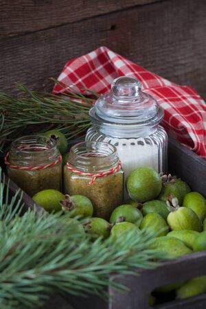 Winter Christmas Feijoa jam bottles with fruit and sugar on the rustic background. Toned. Stock Photo