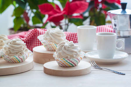 Breakfast wit marshmallow or zephyr with a cup of coffee near Christmas poinsettia. Toned.
