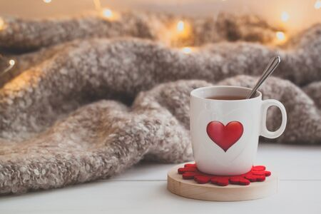 Festive Cup of tea with a smoke and a red heart over the knitted plaid. Toned Stock Photo