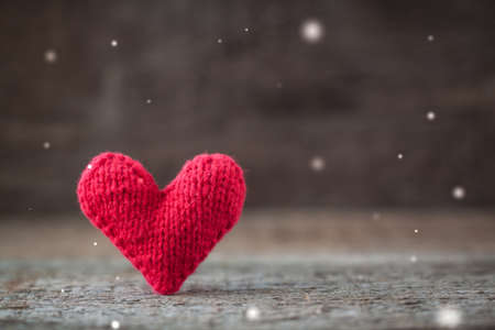 Handmade red knitted Valentine heart on rustic wooden background with fairies effect and copy space. Toned.