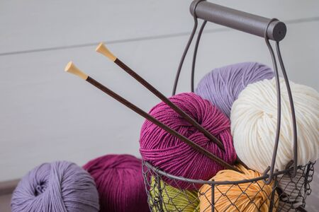 Colorful spring wool yarn in an iron basket with wooden knitting needles. With a copyspace