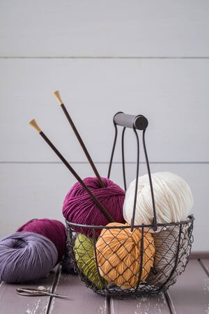 Colorful spring wool yarn in an iron basket with wooden knitting needles and scissors. With a copyspace