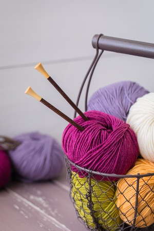 Colorful spring wool yarn in an iron basket with wooden knitting needles. With a copy space Stock Photo