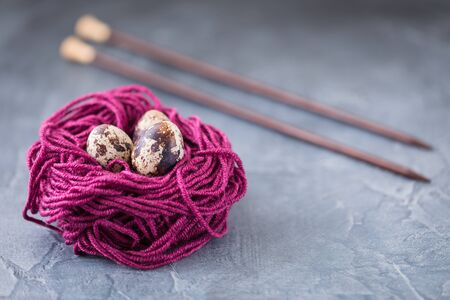 Quail eggs in a violet colorful wool nest with knitting needles. Knitters easter postcard concept. With a copyspace