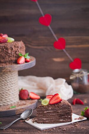 Russian chocolate cake Napoleon with strawberries on the wooden background. Toned.