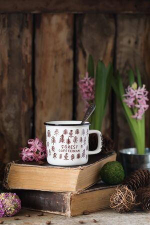 White ceramic cup of coffee on old books on rustic wooden background with cones and hyacinth. Toned. Spring postcard concept 版權商用圖片