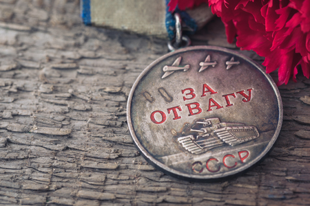 The Old Soviet Medal For Bravery of the Second World War with a red carnation, Victory Day May 9 postcard concept, toned vintage