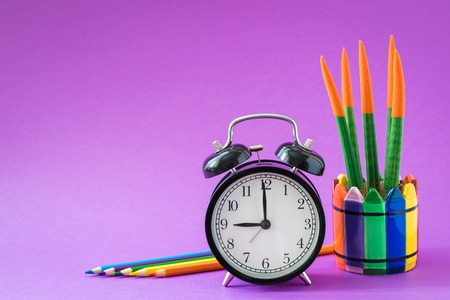Alarm set at 9 o'clock, colorful cactus, rainbow pencils, working school drawing concept, ultraviolet background