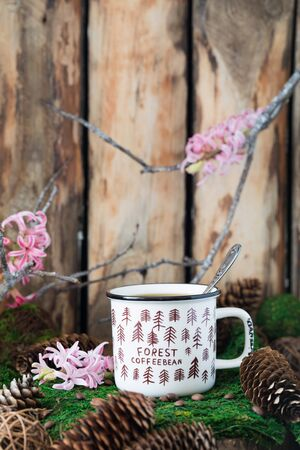 White ceramic cup of coffee on on rustic wooden background with cones and hyacinth. Toned. Spring postcard concept