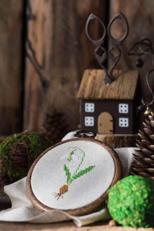 Spring postcard with cross stitched snowdrop on the wooden background. Toned.