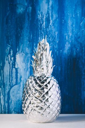 Artificial silver pineapple on blue painted wall background, toned