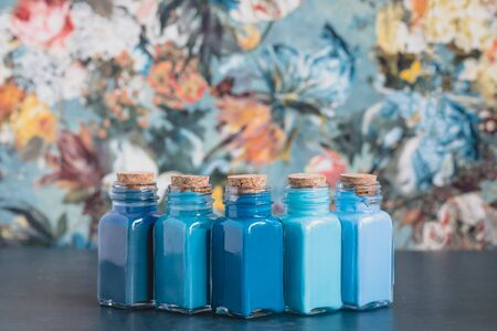 Colorful bottles with blue shades paints on wallpaper background, drawing concept, toned Stock Photo