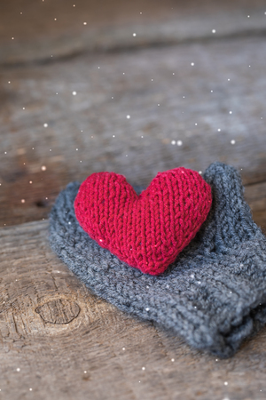 Knitted red heart on the handmade mitt, Valentine's Day postcard, toned