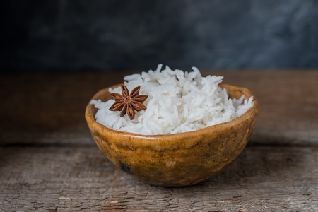 Bowl with white rice on the wooden background, wabi sabi style, toned Stock Photo
