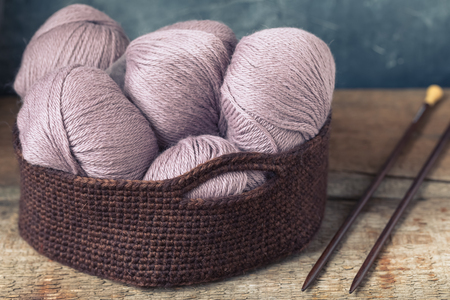 Knitting accessories needles with pink wool yarn in the crocheted basket, toned Standard-Bild - 101219501