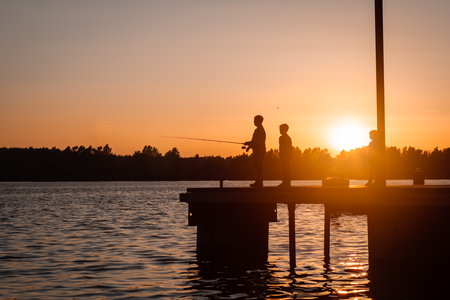 Father and son fishing in the river at sunset