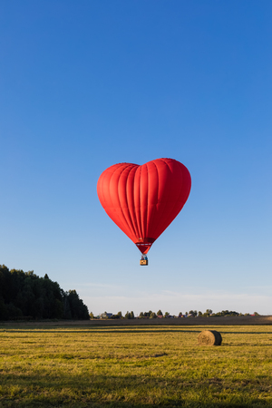 Red heart shaped air balloon flying over the fields with haystacks, toned