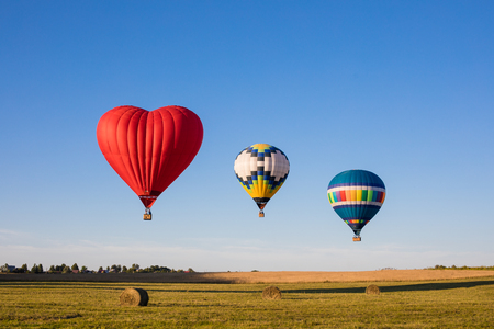 Red heart shaped and colourful air balloon flying over the fields with haystacks, toned