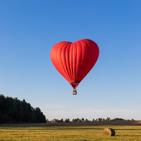Red heart shaped air balloon flying over the fields with haystacks, toned Banque d'images - 106501095